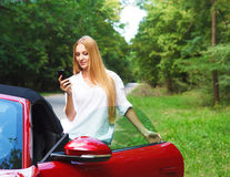Beautiful blond young woman standing near a sports car. With mobile phone Royalty Free Stock Photos