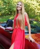 Beautiful blond young woman standing near a  sports car Stock Photos