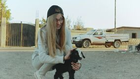 Beautiful blond young woman strokes the black and white goat kid in Dahab, Egypt, Sinai, slow motion, full hd