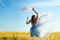 Beautiful blond young woman wearing long blue ball dress and holding white lace umbrella leaning up on wheat field Stock Photo