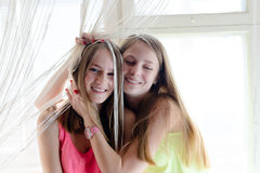 2 beautiful blond young women girlfriends having fun happy smiling hugging sitting on window & looking at camera closeup portrait Royalty Free Stock Photo