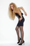 Beautiful blonde. Portrait of beautiful european long haired blonde posing near white wall royalty free stock image