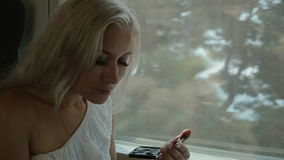 Beautiful blonde applying eye shadow and lip gloss. Sitting in the car of the moving train stock footage