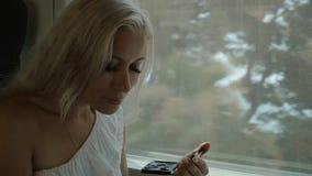 Beautiful blonde applying eye shadow and lip gloss stock footage