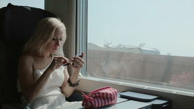 Beautiful blonde applying eye shadow. Sitting in the car of the moving train stock video