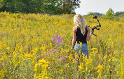 Beautiful blonde archer in field of wildflowers Royalty Free Stock Photography
