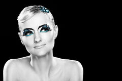 Beautiful blonde with artistic makeup. Over black background royalty free stock image