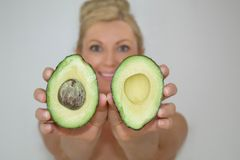 Beautiful blonde avocado woman in front of camera, close-up stock photography