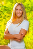 A beautiful blonde on a background of fuzzy foliage Royalty Free Stock Images