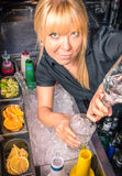 Beautiful blonde Barmaid at Work. Pouring a cocktail in a mixing Glass Stock Image