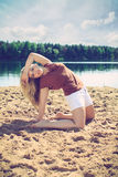 Beautiful blonde on a beach. Beautiful blonde in brown shirt and white shorts kneels in the sand, on a beach, fashion photography Royalty Free Stock Photos
