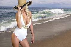 Beautiful blonde on the beach. Classy young blond woman with straw beach hat and a fashionable white bathing suit looks over the secluded sandy Pacific coast Stock Image