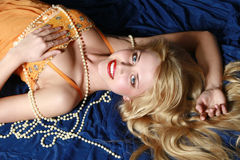 Beautiful blonde with beads. In orange dress Royalty Free Stock Image
