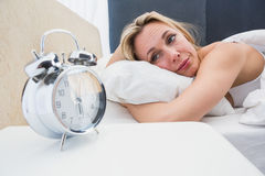 Beautiful blonde in bed with alarm clock Royalty Free Stock Image