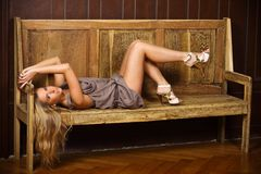 Beautiful blonde on a bench. Beautiful blonde lying on a bench in the interior, studio lighting, castle environment, fashion photography Stock Photos