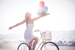 Beautiful blonde on bike ride holding balloons Royalty Free Stock Photos