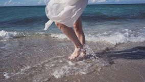 The beautiful blonde in a bikini walking on the beach. The beautiful blonde in a bikini and sunglasses walking on the beach. The wind blows and tosses her hair stock footage