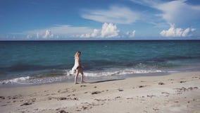 The beautiful blonde in a bikini walking on the beach. The beautiful blonde in a bikini and sunglasses walking on the beach. The wind blows and tosses her hair stock video footage