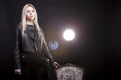 Beautiful blonde on black background with a studio light behind Royalty Free Stock Images