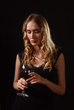 Beautiful blonde in black dress with glass of red wine Stock Images