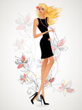 Beautiful blonde in a black dress standing on the background flo Royalty Free Stock Photos