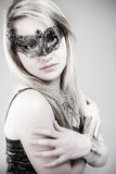 Beautiful blonde in black leather jacket, mysterious mask and si stock image