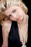 Beautiful blonde in black with pearls. Blonde girl in black blouse with white pearls royalty free stock images