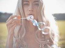 Beautiful blonde blowing bubbles Royalty Free Stock Images