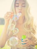Beautiful blonde blowing bubbles Stock Image