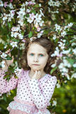 Beautiful blonde blue-eyed girl. In a flowering apple orchard Stock Photos
