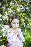 Beautiful blonde blue-eyed girl. In a flowering apple orchard Royalty Free Stock Photo