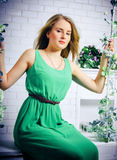 The beautiful blonde with blue eyes in the green dress on a swin. G with flowers Stock Photo