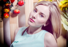 The beautiful blonde with blue eyes seriously looking. In blue Stock Photos