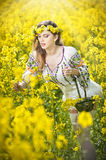 Beautiful blonde with blue eyes smiling and enjoying the bright yellow flowers of rapeseed Stock Images