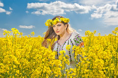 Beautiful blonde with blue eyes smiling in rapeseed field Royalty Free Stock Photo