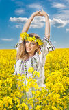 Beautiful blonde with blue eyes smiling in rapeseed field Royalty Free Stock Photos