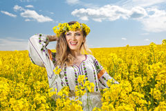 Beautiful blonde with blue eyes smiling in rapeseed field stock photo