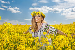 Beautiful blonde with blue eyes smiling in rapeseed field Royalty Free Stock Image