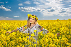 Beautiful blonde with blue eyes smiling in rapeseed field Royalty Free Stock Photography