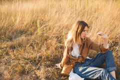 Beautiful blonde in blue jeans, a white shirt and brown jacket is sitting in a field Stock Image