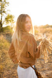 Beautiful blonde in blue jeans, a white shirt and brown jacket walking in the field, laughing and holding a bouquet with spikelets Royalty Free Stock Images