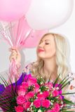 Beautiful blonde with a bouquet of flowers roses and with pink and white balls. Joyful emotions. Celebration. royalty free stock photo