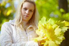 Beautiful blonde with a bouquet maple leaves Stock Photography
