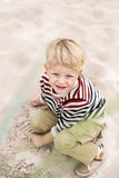 Beautiful blonde boy playing with sand on the beach. Oudoor portrait Stock Photos