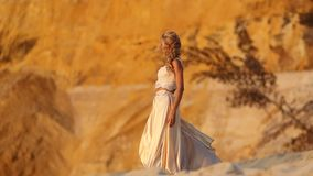 Beautiful bride is wearing fashion flying dress and wreath in the great desert in Dubai.