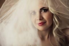 Beautiful blonde bride. daylight. studio shot. Emotive portrait of a smiling beautiful blonde bride with vapory white veil. daylight. Close up. Studio shot Royalty Free Stock Image