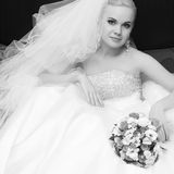 Beautiful blonde bride with great vapory veil. Portrait of a beautiful blonde bride with great vapory veil and wedding bouquet. Black and white (monochrome) Stock Images