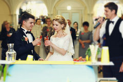 Beautiful blonde bride and handsome groom drinking cocktails royalty free stock photos