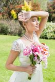 Beautiful blonde bride holding arm to forehead Royalty Free Stock Photo