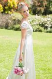 Beautiful blonde bride holding bouquet looking at camera Stock Images